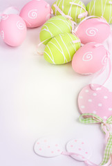 Easter pink and green painted eggs on white background and copy space.