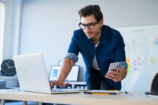 Programmer, web developer, designer working at office comparing mobile and desktop website versions