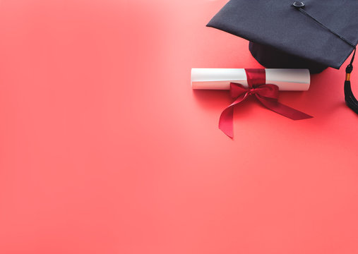 academic hat with diploma on red background