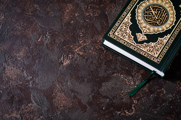 Islamic Book Koran on dark vintage background with arabic calligraphy that means the Holy Quran