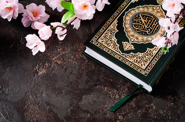 Islamic Book Koran and spring flowers brunch on dark background with arabic calligraphy that means the Holy Quran. Sring concept. Selective focus