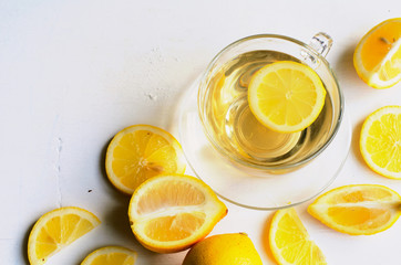 Lemon tea in a transparent cup on white background with slices of lemon