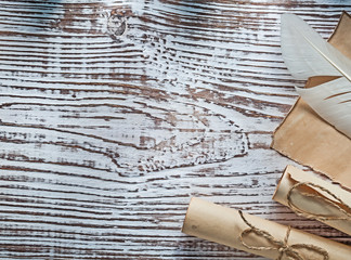 Medieval parchment roll of paper plume on vintage wooden board