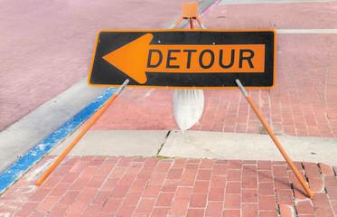 Black and orange detour sign on red brick sidewalk.