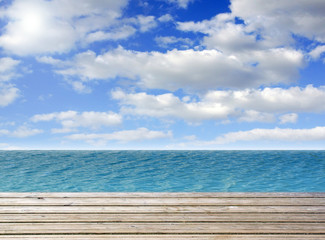Wooden plank with turquoise sea or ocean and blue sky with some clouds, copy space for individual text - summer holidays