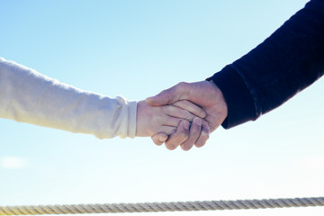 Female male couple touching hands on sunny outdoors background. Close up view of emotional feelings