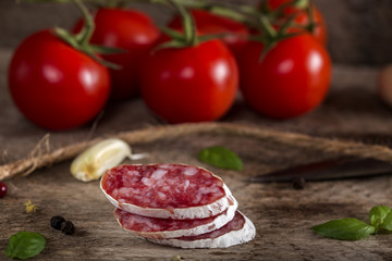 Italian salami slices on wood with cherry tomatoes, garlic and herbs