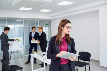 Young businesswoman working on  background of colleagues in the office.