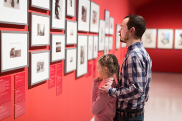 Father and girl exploring exhibition of photos