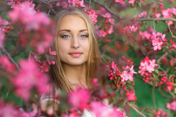 Portrait of a beautiful blonde girl with long hair and perfect make up among pink cherry blossoms in spring.