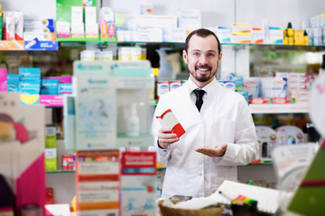 Positive man pharmacist showing pills