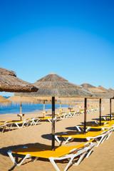 Straw umbrellas on ocean beach in Algarve Portugal, sunny outdoors background