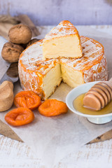 Soft cheese with cut off slice creamy texture, orange rind with mold, French, German, Alps, honey dipper, walnuts, dried apricots, knife, top view