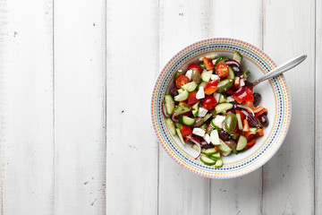 Fresh Greek salad in a big bowl on white wooden background, top view
