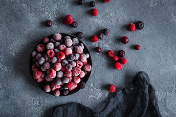 Frozen raspberry, blueberry, cranberry on dark background. Frozen fruit. Top view, flat lay