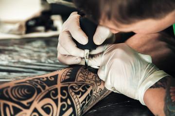 Master tattoo artist in gloves makes tattoo on hand men