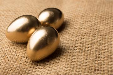 Beautiful festive golden quail eggs, easter background