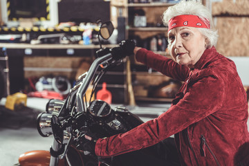 Serene pensioner locating on motorcycle in garage