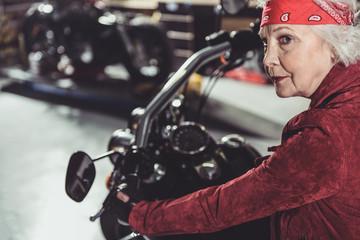 Cool retiree driving bike in mechanic shop
