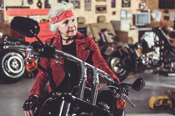 Pensive retiree locating on bike in mechanic shop