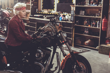 Cheerful pensioner situating on motorcycle in garage
