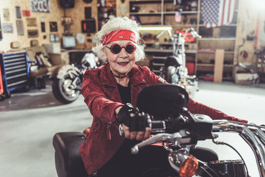 Outgoing grandmother driving motorcycle in mechanic shop