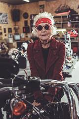 Pleased old woman bracing on bike