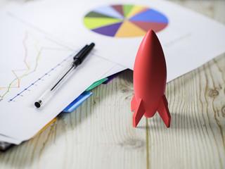 rocket model on desk with pie chart