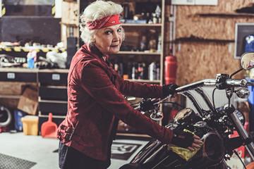 Smiling retiree polishing motorcycle in mechanic shop