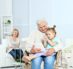 Grandparents and their granddaughter with gadgets at home