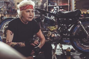 Serene female retire fuming near motorcycle