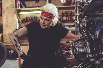 Calm grandmother situating near bike in garage