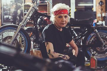 Calm grandmother locating near bike
