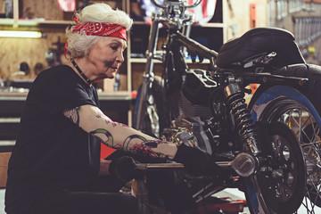 Serene old woman reconditioning bike in garage