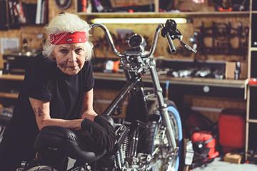 Calm tired pensioner standing near bike in garage