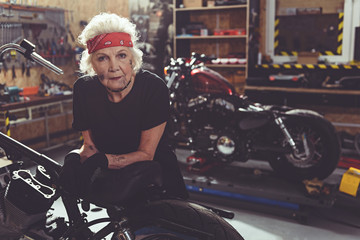 Cool female retiree locating next to motorcycle