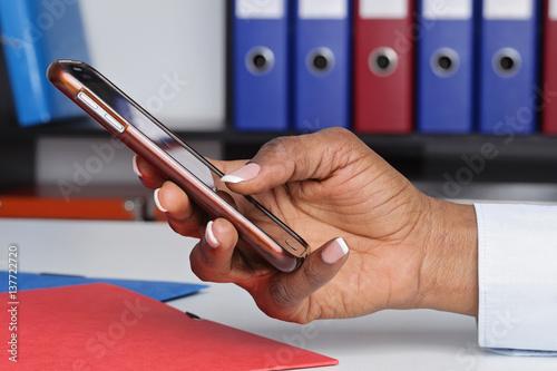Main femme noire formant un numéro sur un téléphone portable au