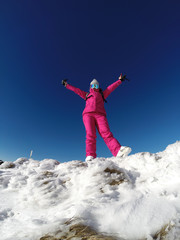 Young skier on the top of snowy mountain