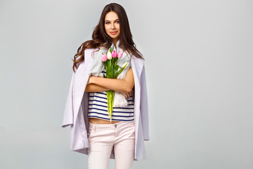 Fashion photo of a beautiful young woman with tulips in her hand .she dressed  in a beautiful coat, scarf, pants and T-shirt with stripes.Spring concept. March 8. beautiful girl in stylish clothes.