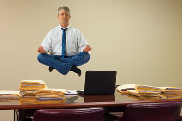 Work related stress relief with yogaa with man hovering over stacks of paperwork and computer on conference table