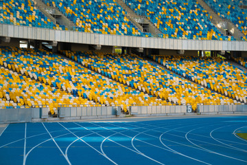 Empty colorful stadium seats and running tracks.