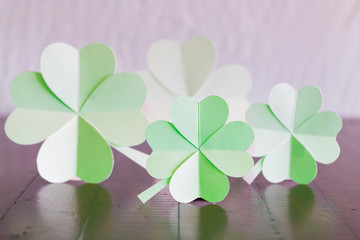 Hand made 4 paper lucky four-leaf clovers on the rustic wooden table.
