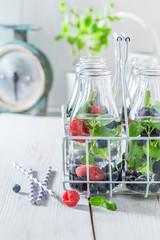 Fresh soda in bottle with raspberries, blueberries and blackberries