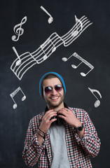 Pretty smiling young man with sunglasses listening music in headphones with musically drawings