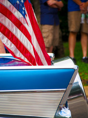 Detail of a classic car with an American flag attached driving in a Fourth of July Parade.