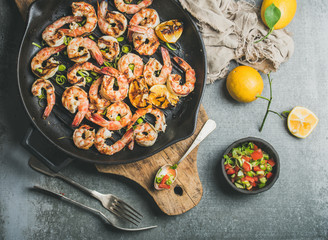 Seafood dinner. Grilled tiger prawns in cast iron grilling pan with lemon, leek, chili pepper and mint salsa sauce over grey concrete background, top view. Slow food concept