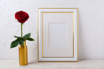 Frame mockup with burgundy red rose in golden vase