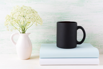 Black coffee mug mockup with books and tender white flowers