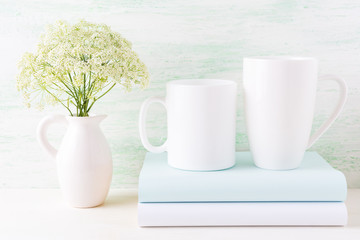 Two white mugs mockup with books and white flowers in pitcher