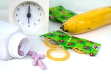 Condom and medicine concept eat medicine for power strength clock show 6 oclock.